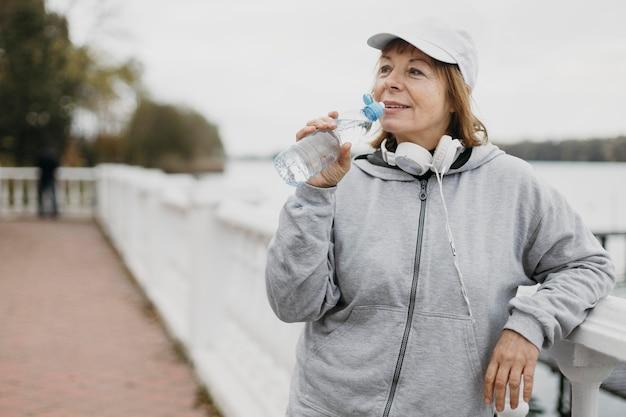 Mulher idosa bebendo água ao ar livre após malhar