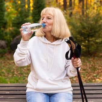 Mulher idosa bebendo água ao ar livre durante uma caminhada