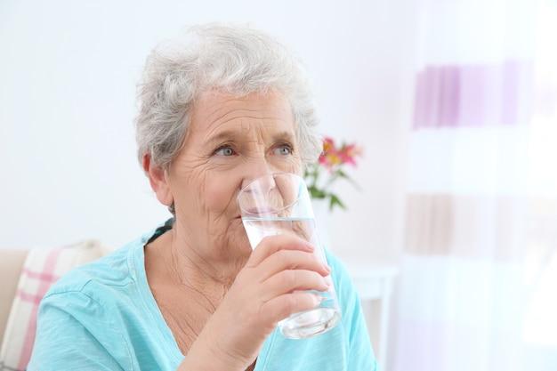 Mulher idosa bebendo água em casa. conceito de aposentadoria