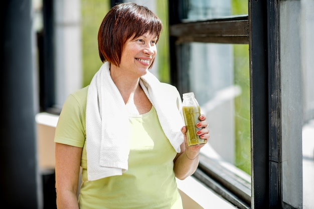 Mulher idosa bebendo smoothie após o treinamento dentro de casa perto da janela