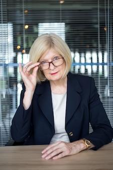 Mulher idosa bem sucedida ajustando óculos na mesa