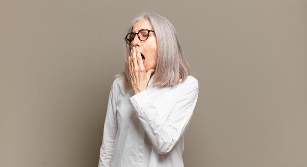 Mulher idosa bocejando preguiçosamente no início da manhã, acordando e parecendo sonolenta, cansada e entediada Foto Premium