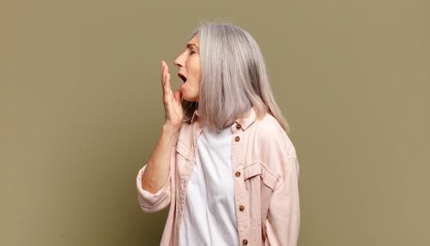 Mulher idosa bocejando preguiçosamente no início da manhã, acordando e parecendo sonolenta, cansada e entediada