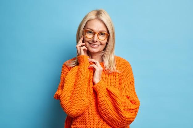 Mulher idosa bonita com cabelo loiro, pele saudável tocando rosto, sorrindo com ternura, usa modelo de suéter de malha laranja