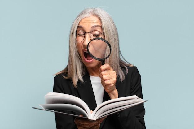 Mulher idosa bonita com um livro e uma lupa