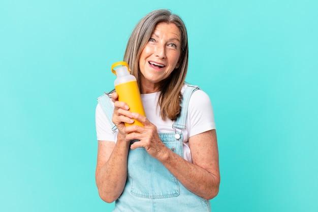Mulher idosa bonita com uma garrafa térmica de café