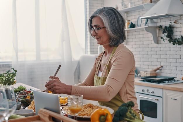 Mulher idosa bonita de avental cozinhando um jantar saudável enquanto passa um tempo em casa