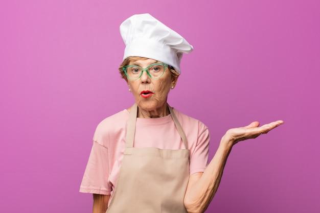 Mulher idosa bonita e madura parecendo surpresa e chocada, com o queixo caído segurando um objeto com a mão aberta ao lado