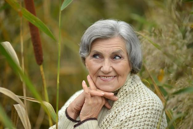 Mulher idosa bonita feliz no parque de outono