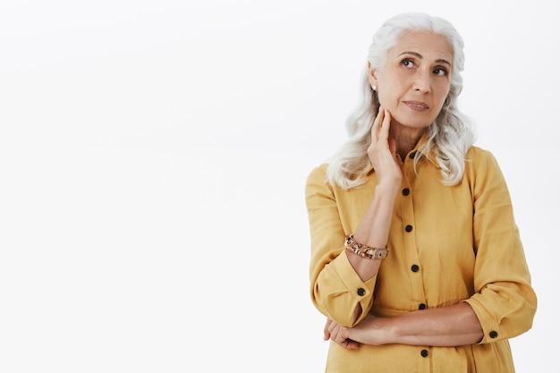 Mulher idosa bonita sonhadora olhando o canto esquerdo superior pensativo