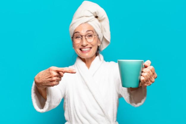 Mulher idosa bonita vestindo roupão de banho e tomando um café