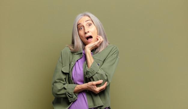 Mulher idosa boquiaberta em choque e descrença, com a mão na bochecha e os braços cruzados, sentindo-se estupefata e espantada