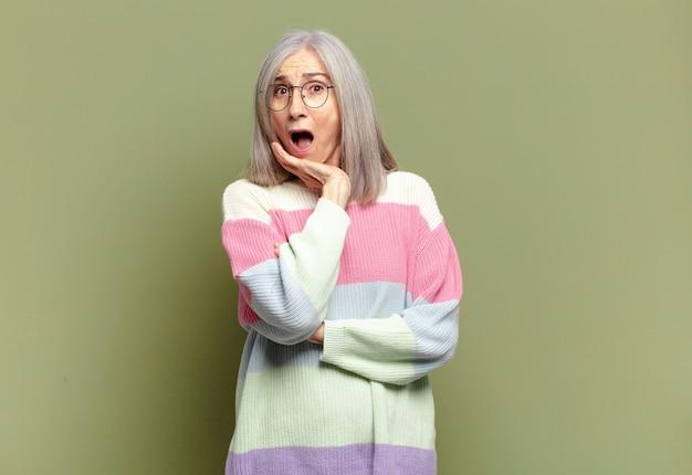 Mulher idosa boquiaberta em choque e descrença, com a mão na bochecha e os braços cruzados, sentindo-se estupefata e surpresa