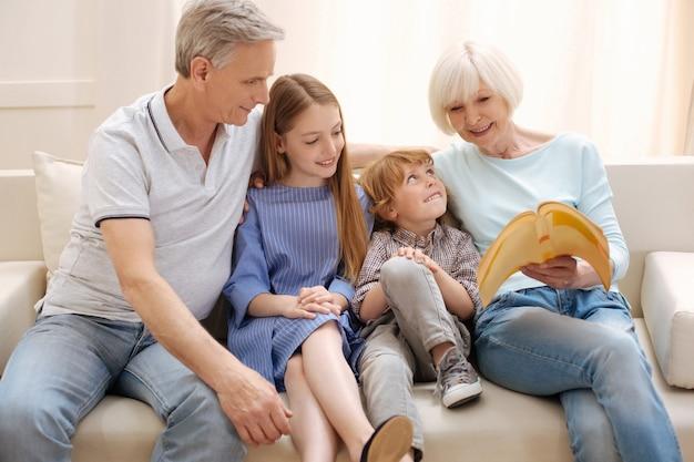 Mulher idosa brilhante original lendo uma história para a neta e o neto enquanto eles faziam uma visita no fim de semana