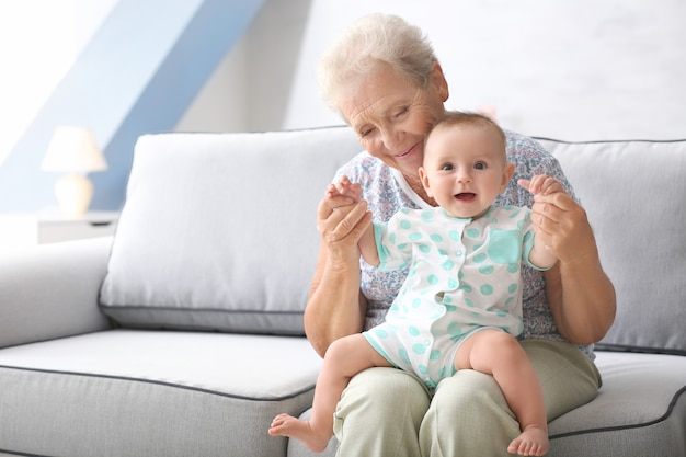 Mulher idosa brincando com o netinho em casa