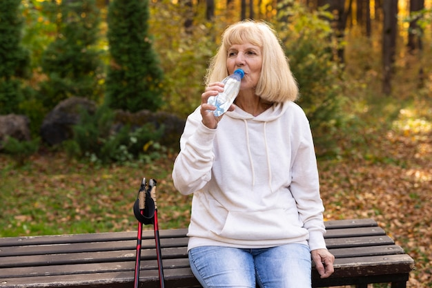 Mulher idosa caminhando ao ar livre e bebendo água