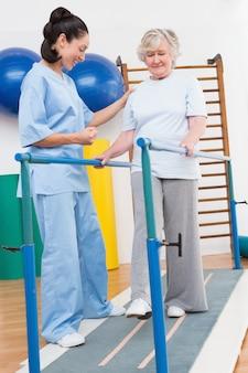 Mulher idosa caminhando com barras paralelas com terapeuta