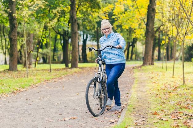 Mulher idosa caminhando no parque com uma bicicleta
