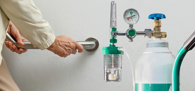 Mulher idosa caminhando para o tanque de oxigênio médico de emergência.