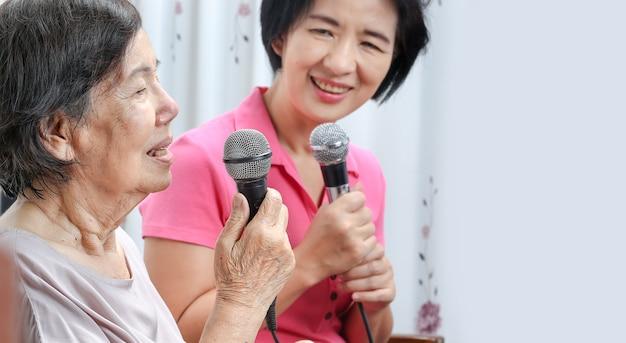 Mulher idosa canta uma música com a filha em casa.