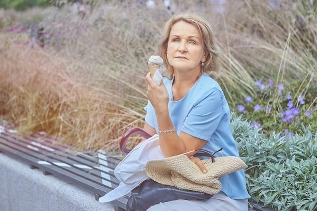 Mulher idosa caucasiana bonita de 60 anos está sentada no banco