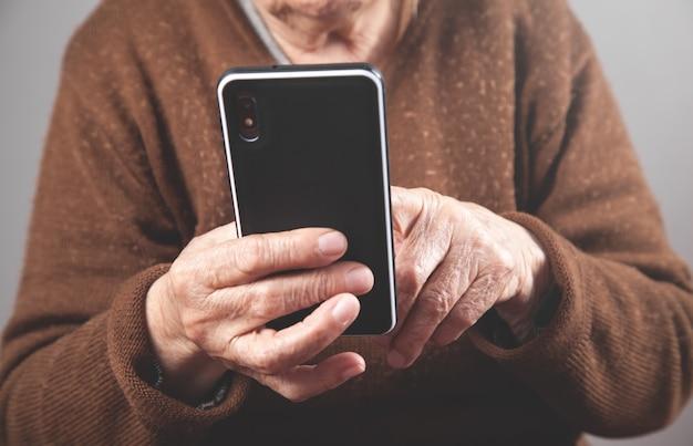 Mulher idosa caucasiana usando smartphone.
