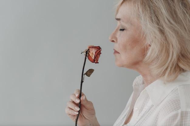 Mulher idosa chateada em vestido branco segurando murcha uma flor rosa velha e seca