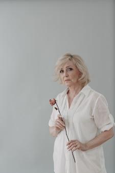 Mulher idosa chateada em vestido de branco segura solteira murcha e flor de rosa velha e seca