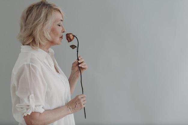 Mulher idosa chateada em vestido de branco segure murcha uma flor rosa velha e seca.