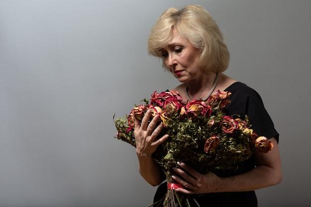 Mulher idosa chateada segura buquê de flores rosa velho seco murcho.