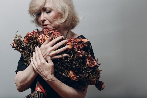 Mulher idosa chateada segurando conceito de velhice buquê de flores de rosa murcha seco