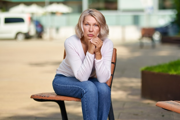 Mulher idosa chateada, sentada em um banco na rua.