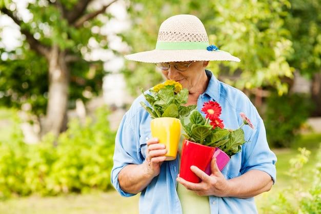 Mulher idosa cheirando flores