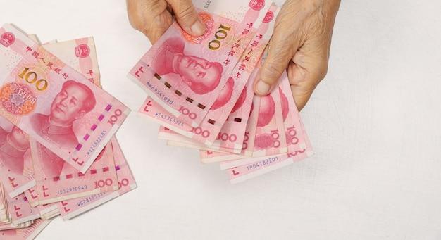 Mulher idosa chinesa contando dinheiro para o pagamento