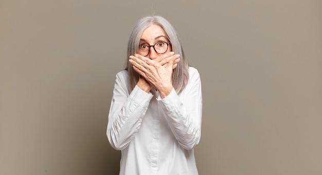 Mulher idosa cobrindo a boca com as mãos com uma expressão chocada e surpresa, mantendo um segredo ou dizendo oops
