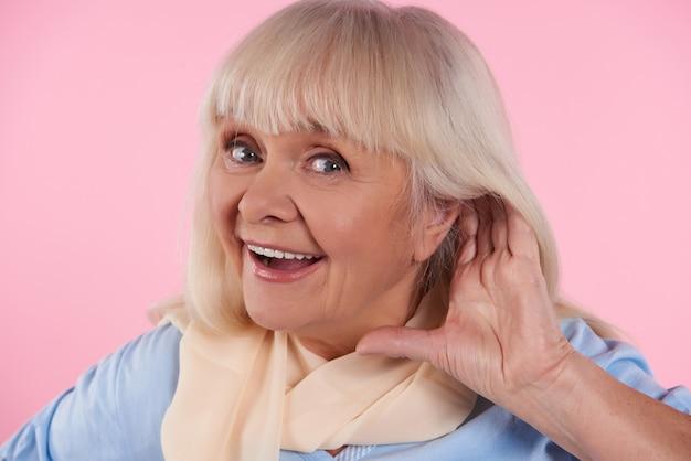 Mulher idosa coloca a mão no ouvido