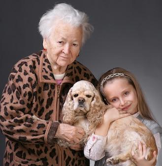 Mulher idosa com a neta e um cachorro