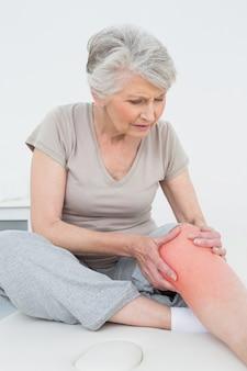 Mulher idosa com as mãos em um joelho dolorido