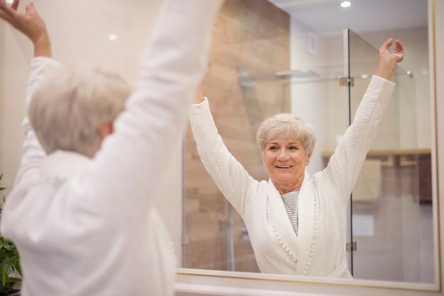 Mulher idosa com as mãos levantadas
