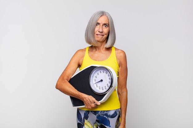 Mulher idosa com balança, conceito de perda de peso