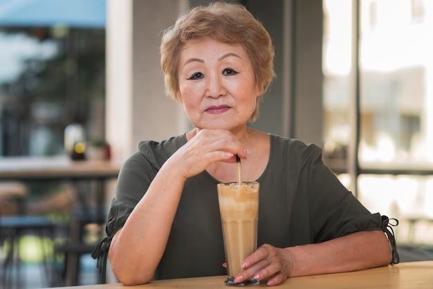 Mulher idosa com bebida mediana
