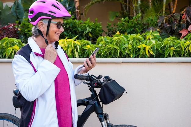Mulher idosa com bicicleta e capacete rosa para para ler a mensagem em seu telefone inteligente