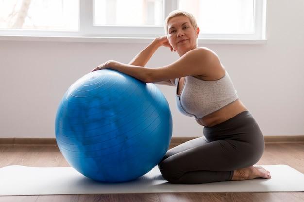 Mulher idosa com cabelo curto usando bola de fitness