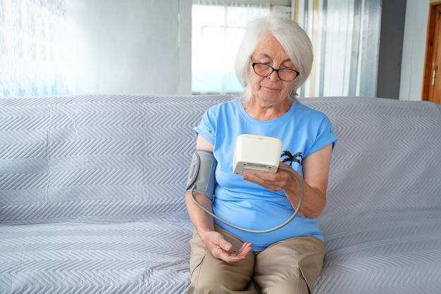 Mulher idosa com cabelos grisalhos e óculos está sentada no sofá e medindo a pressão arterial com monitor automático de pressão arterial