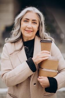 Mulher idosa com caixas de comida para levar