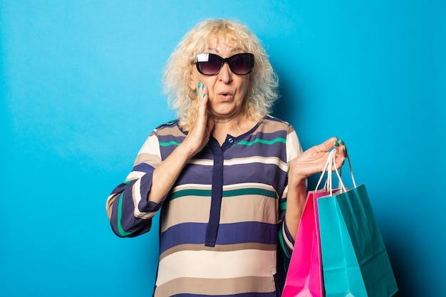 Mulher idosa com cara de surpresa segurando sacolas de compras na superfície azul