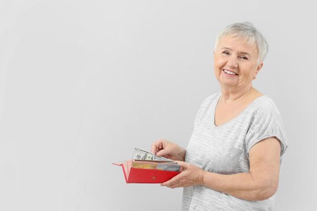 Mulher idosa com carteira e dinheiro