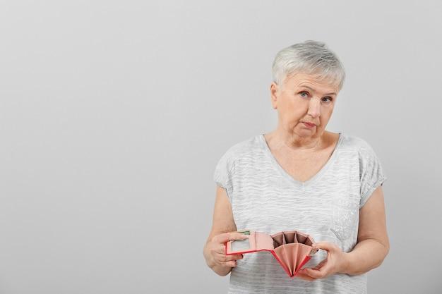 Mulher idosa com carteira vazia em fundo claro