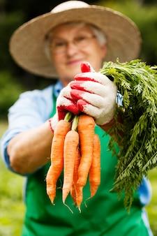 Mulher idosa com cenouras
