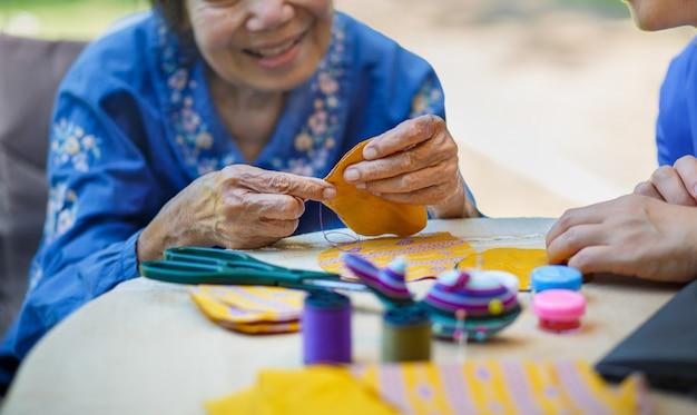 Mulher idosa com cuidador na terapia ocupacional de artesanato com agulha